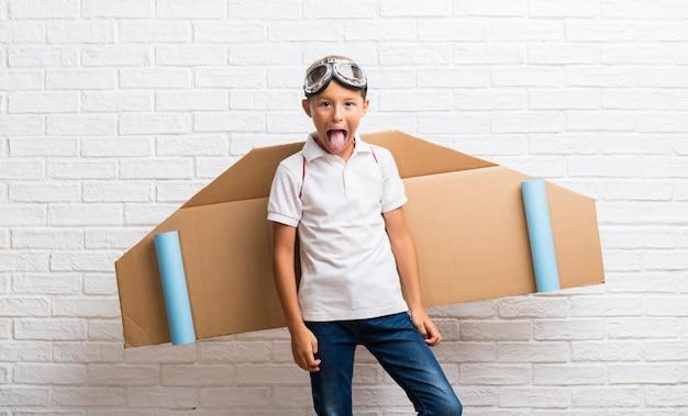 Ragazzo che gioca con le ali di aeroplano di cartone sul suo indietro mostrando la lingua alla fotocamera con sguardo divertente