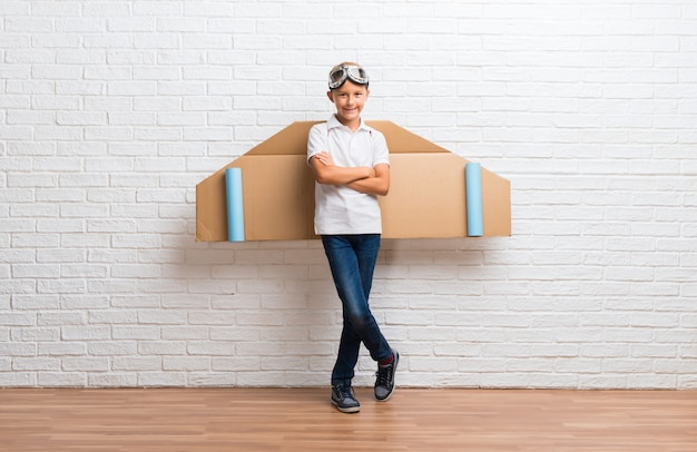 Ragazzo che gioca con le ali di aeroplano di cartone sulla schiena tenendo le braccia incrociate