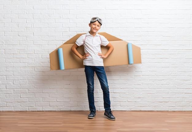 Ragazzo che gioca con le ali di aeroplano di cartone sulla sua schiena in posa con le braccia all'anca