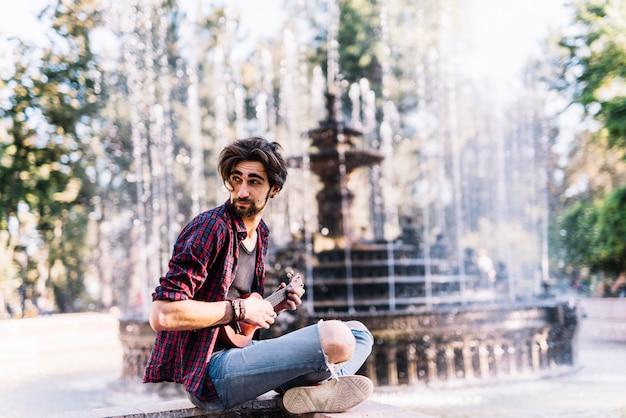 Ragazzo che gioca gli ukelele che si siedono su una fontana