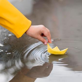 Ragazzo che gioca in acqua con un primo piano di barca di carta