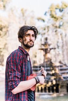 Ragazzo che gioca l'ukelele da una fontana