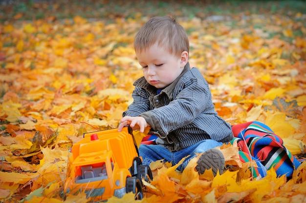 Ragazzo che gioca macchina in foglie di autunno gialle