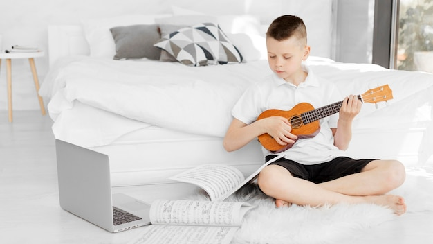 Ragazzo che guarda tutorial online su come giocare all'ukulele