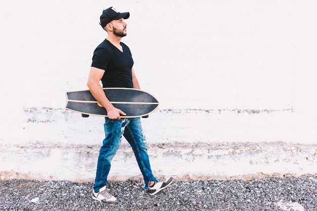 Ragazzo che indossa jeans e berretto, tenendo il suo skateboard sul braccio sopra il muro bianco invecchiato