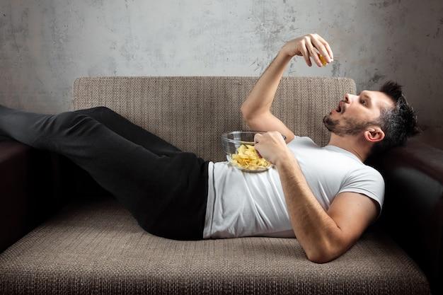Ragazzo che indossa una camicia bianca è sdraiato sul divano, mangia patatine e guarda un canale sportivo.