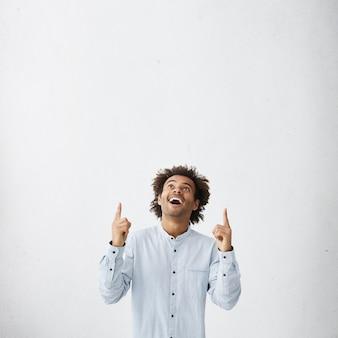 Ragazzo che indossa una camicia bianca elegante che punta e guarda con un sorriso verso l'alto