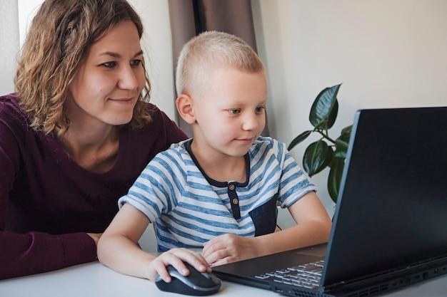 Ragazzo che lavora ad un computer insieme a sua madre a casa. e-lezioni, educazione per bambini.