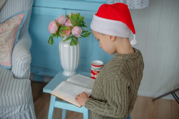 Ragazzo che legge un libro con cappello di babbo natale