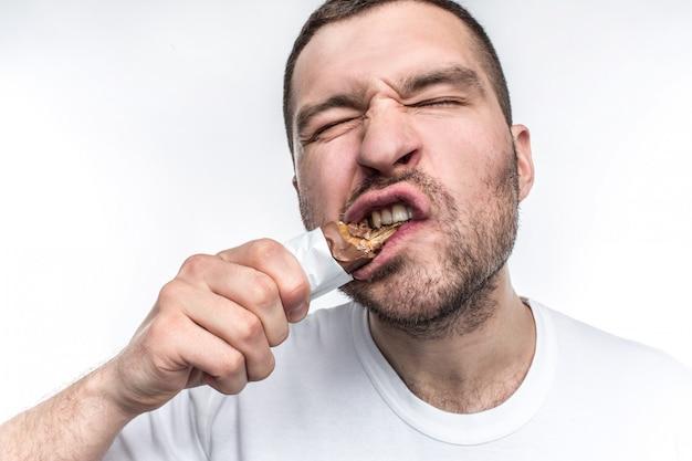 Ragazzo che mangia la barra di cioccolato dolce con il torrone