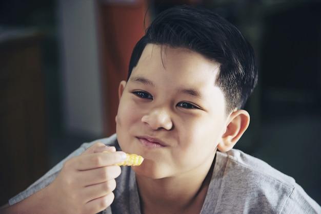 Ragazzo che mangia patatine fritte con salsa immersa sul tavolo di legno bianco