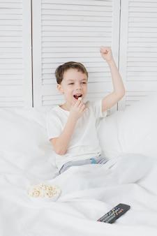 Ragazzo che mangia popcorn seduto nel letto e guardare la tv