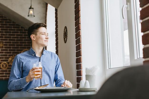 Ragazzo che mangia una birra in un ristorante