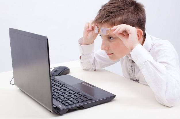 Ragazzo che per mezzo del suo computer portatile