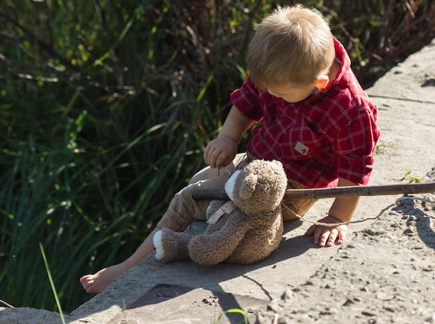 Ragazzo che pesca dalla riva con il suo orso giocattolo