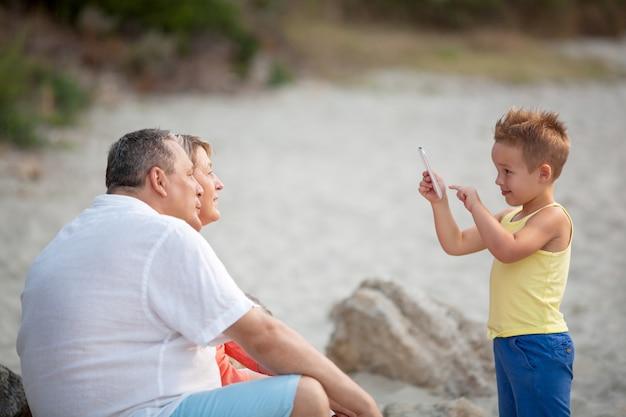 Ragazzo che prende la foto del telefono dei nonni all'aperto