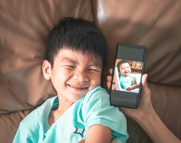 Ragazzo che si confronta con la sua foto del bambino