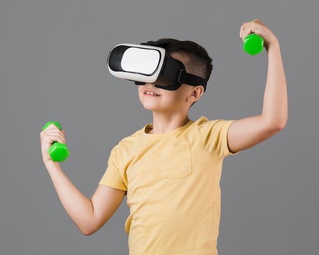 Ragazzo che si esercita con i pesi mentre indossa le cuffie da realtà virtuale