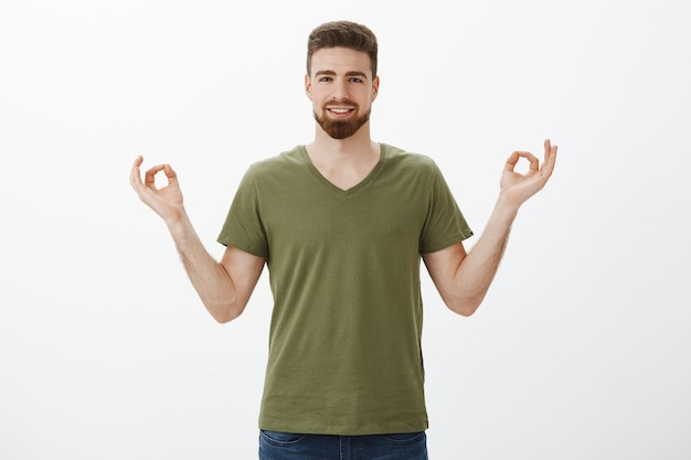 Ragazzo che si sente calmo e rilassato, senza stress grazie alle nuove pillole, sorridendo ampiamente e sollevato tenendosi per mano in zen, gesto del loto sorridente soddisfatto meditando e praticando yoga sul muro bianco