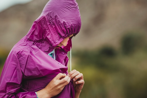 Ragazzo che si veste con un impermeabile per non bagnarsi con la pioggia