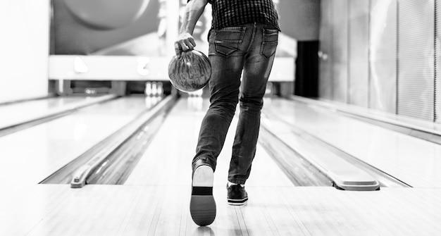Ragazzo che sta per lanciare un concetto di hobby e tempo libero della palla da bowling