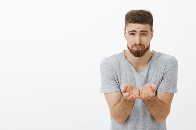Ragazzo che suggerisce che il suo cuore sia un ragazzo carino e carino. affascinante brunet caucasico bello e maschile che tiene i palmi vicino al petto come se trasportasse qualcosa di fragile tra le braccia in piedi sopra il muro grigio