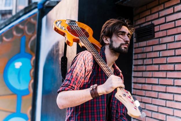 Ragazzo che tiene la chitarra elettrica accanto al muro di mattoni