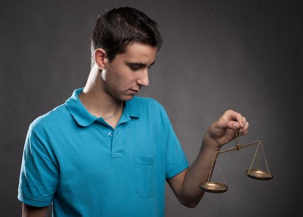 Ragazzo che tiene una scala della giustizia su una priorità bassa grigia