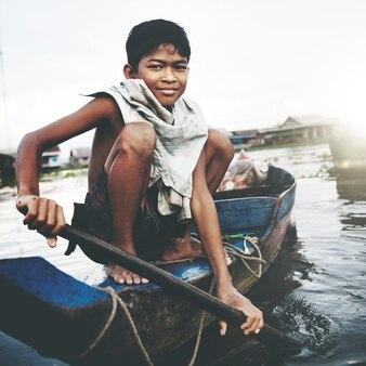 Ragazzo che viaggia in barca nel villaggio galleggiante.