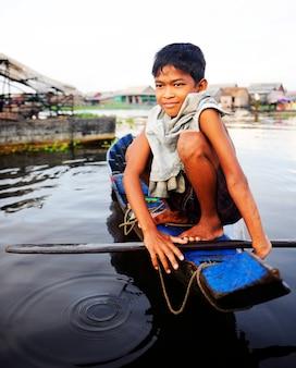 Ragazzo che viaggia in barca nel villaggio galleggiante