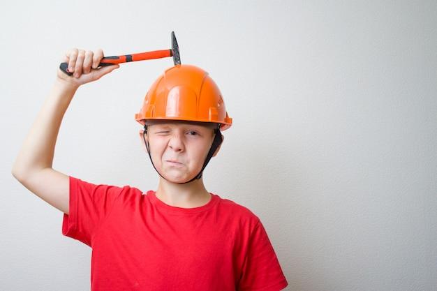 Ragazzo con casco, cappello duro. il giovane costruttore con la faccia garrata bussa con il martello sulla testa