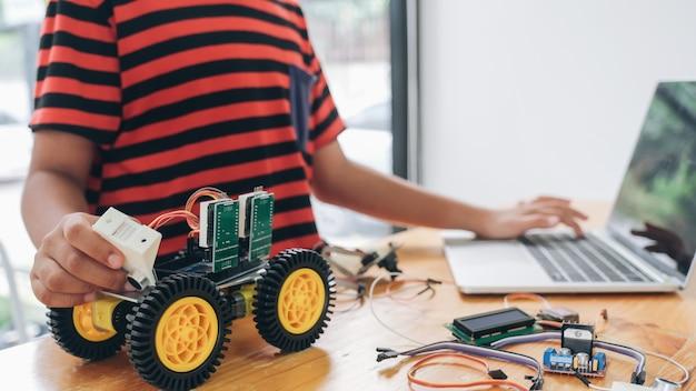 Ragazzo con computer tablet pc programmazione giocattoli elettrici e robot da costruzione.