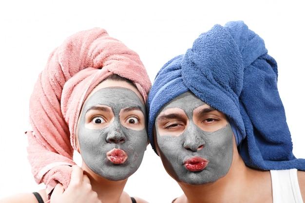 Ragazzo con donna invia un bacio d'aria, maschera per la pelle, crea una maschera per la pelle insieme, divertente coppia di innamorati, foto isolata ruolo emotivo di genere