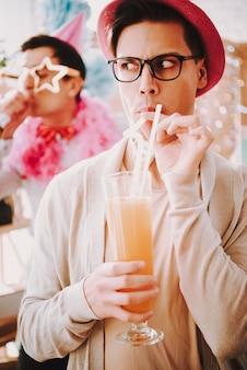 Ragazzo con gli occhiali con un cocktail a una festa gay.