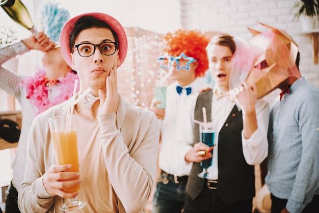 Ragazzo con gli occhiali con un cocktail a una festa gay