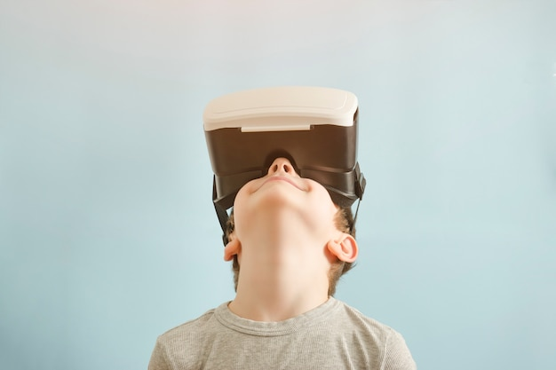 Ragazzo con gli occhiali della realtà virtuale. sfondo blu