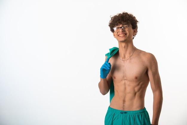 Ragazzo con i capelli ricci in occhiali optique che mostra i suoi muscoli del corpo dopo l'allenamento.