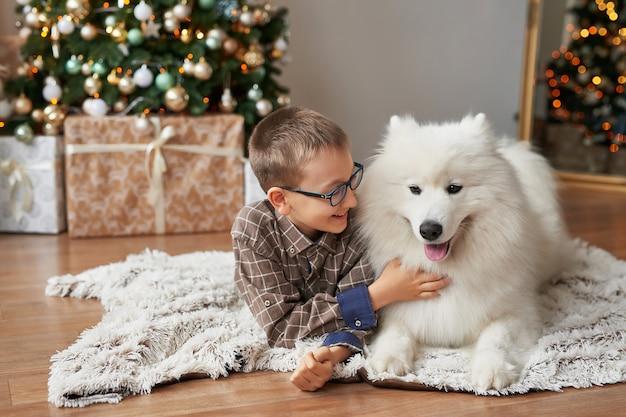 Ragazzo con il cane vicino all'albero di natale su natale
