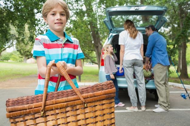 Ragazzo con il cestino di picnic mentre famiglia nella priorità bassa al circuito di collegamento di automobile