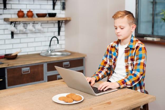 Ragazzo con il portatile in cucina