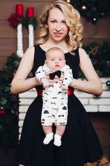 Ragazzo con la bella mamma bionda che abbraccia nella casa decorata per natale