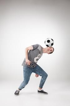 Ragazzo con pallone da calcio su grigio