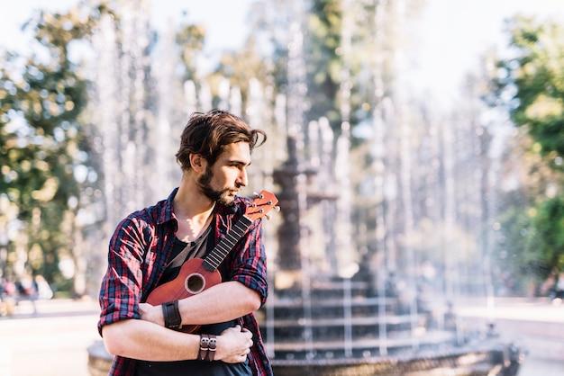 Ragazzo con ukelele di fronte a una fontana
