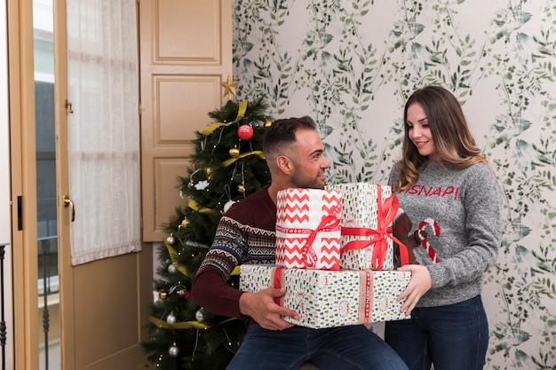 Ragazzo con un mucchio di regali e signora attraente vicino all'albero di natale