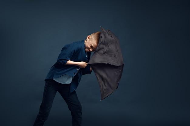 Ragazzo con una faccia spaventata tiene l'ombrello in studio