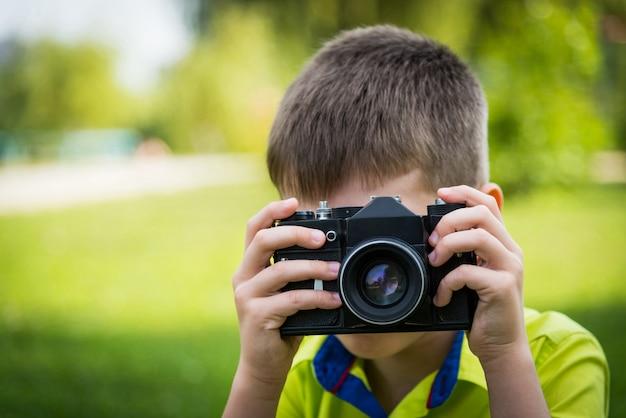 Ragazzo con una macchina fotografica d'epoca.