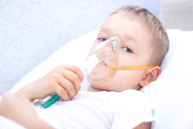 Ragazzo con una maschera per inalatore - problemi respiratori nell'asma. un ragazzo con una maschera per inalatore giace a letto e respira adrenalina. concetto sanitario e bambino malato, coronavirus, bronchite, polmonite