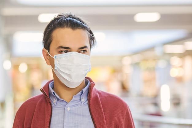 Ragazzo con una maschera protettiva al centro commerciale