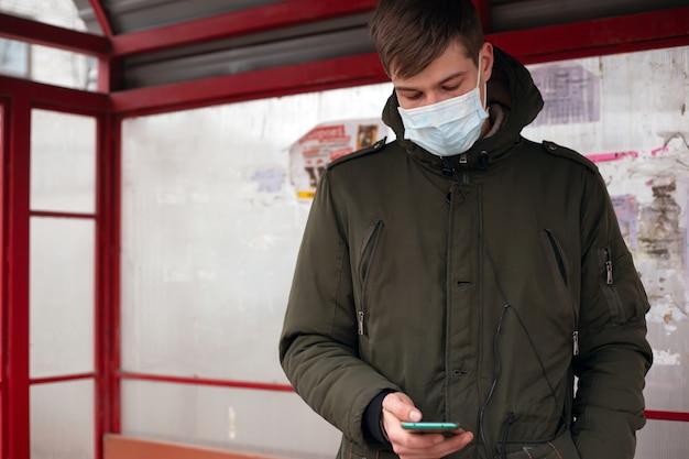 Ragazzo con una mascherina medica si trova alla fermata dell'autobus. isolato per evitare la malattia virale raffreddore da varicella covid-19 influenza morbillo.