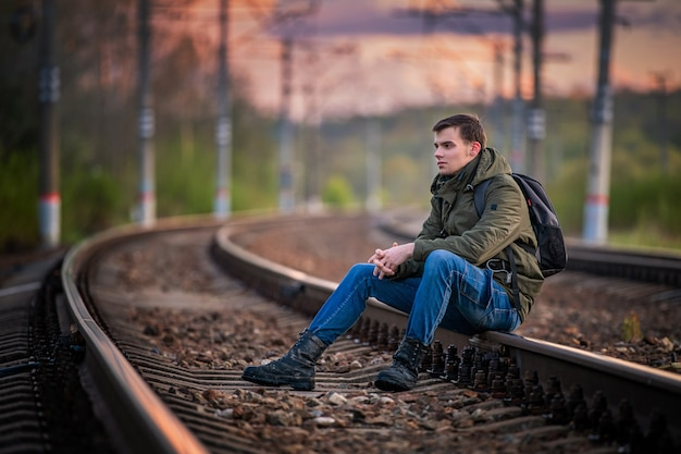 Ragazzo con uno zaino viaggia, si siede sui binari della ferrovia